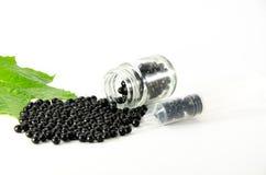 Schwarze Pillen gelegt auf einen weißen Hintergrund und in eine Glasflasche Lizenzfreie Stockfotos