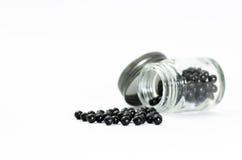 Schwarze Pillen gelegt auf einen weißen Hintergrund und in eine Glasflasche Lizenzfreie Stockfotografie