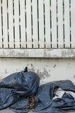 Schwarze Plastikabfalltaschenfront des Zaunhauses Lizenzfreies Stockfoto