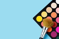 Schwarze Plastikpalette von gelb, rot hell gefärbt, Rosa, orange Lidschatten und große eine Make-upbürste, die auf legt lizenzfreies stockfoto