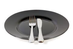 Schwarze Platte, Gabel und Messer Lizenzfreies Stockfoto