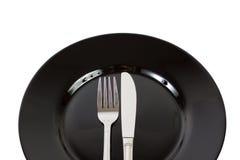 Schwarze Platte, Gabel und Messer Stockfoto