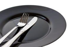 Schwarze Platte, Gabel und Messer Lizenzfreies Stockbild