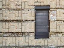 Schwarze Rollemetalltür gegen alte helle Backsteinmauer, Durchgang zum Speicher oder Theater, hinterer Ausgang lizenzfreies stockbild
