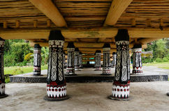 Schwarze Säulen mit weißen Zeichnungen unter ein Haus an einem alten Batak-Dorf Lizenzfreie Stockbilder