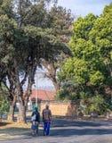 Schwarze südafrikanische Paare, die in eine Wohnstraße gehen lizenzfreie stockfotografie