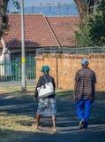 Schwarze südafrikanische Paare, die in eine Wohnstraße gehen stockfotografie