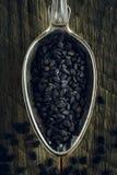 Schwarze Samen des indischen Sesams in einem Löffel lizenzfreie stockbilder