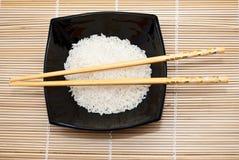 Schwarze Schüssel mit Reis und Ess-Stäbchen lizenzfreie stockbilder