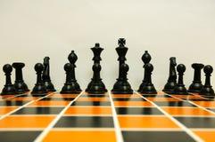 Schwarze Schachfiguren ausgerichtet auf Schachbrett Lizenzfreies Stockfoto