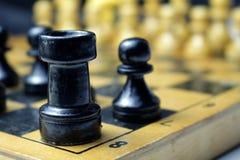 Schwarze Schachfiguren der Turm und das Pfand auf dem Brett Lizenzfreie Stockfotos