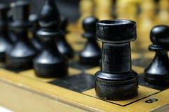 Schwarze Schachfiguren der Turm und das Pfand auf dem Brett Stockfotos