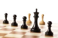 Schwarze Schachfiguren mit weißen Pfand im Hintergrund Stockfotos