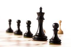 Schwarze Schachfiguren mit weißen Pfand im Hintergrund auf einem Schachbrett Stockbild