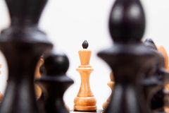 Schwarze Schachfiguren und weißer König Stockfoto