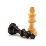 Schwarze Schachköniglüge nahe weißen Fahrwerkbeinen des Siegers Lizenzfreies Stockbild