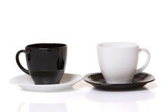 Schwarze Schale auf der weißen Platte und weiße Schale auf dem Schwarzblech stockbild