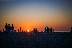 Schwarze Schattenbilder von Leuten auf dem Strand im Sonnenunterganglicht der orange Sonne stockfotografie