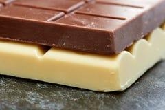 Schwarze Schokolade liegt auf der weißen Schokoladennahaufnahme Lizenzfreie Stockfotografie