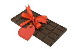 Schwarze Schokolade mit rotem Farbband und Marke   Lizenzfreie Stockbilder