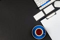 Schwarze Schreibtischtabelle des Büros mit weißem Computer, Visitenkartefreiem raum, Blume, Kaffeetasse und Stift Lizenzfreie Stockbilder