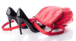 Schwarze Schuhe der hohen Absätze mit einer roten Handtasche Stockfotografie