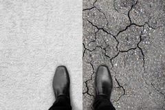Schwarze Schuhe, die auf Teppich und Erde stehen Stockfoto