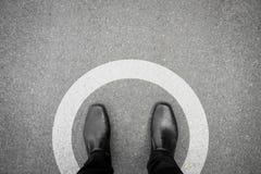 Schwarze Schuhe, die im weißen Kreis stehen Stockfoto