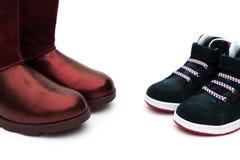 Schwarze Schuhe für Sohn und Rot eine für Mutter als Abstammungskonzept Lizenzfreie Stockfotos