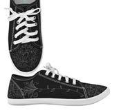 Schwarze Schuhe mit weißen Spitzeen und Blumenmuster stockfotos