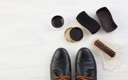 Schwarze Schuhe und Creme mit Bürstensorgfalt Lizenzfreie Stockfotografie