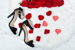 Schwarze Schuhe und ein Blumenstrauß von roten Rosen auf einem weißen Pelz Rotes candl Stockfoto
