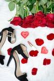 Schwarze Schuhe und ein Blumenstrauß von roten Rosen auf einem weißen Pelz Rotes candl Stockbild