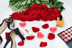Schwarze Schuhe und ein Blumenstrauß von roten Rosen auf einem weißen Pelz Rotes candl Lizenzfreie Stockbilder
