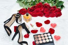 Schwarze Schuhe und ein Blumenstrauß von roten Rosen auf einem weißen Pelz Rotes candl Stockfotos