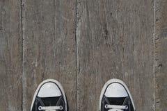 Schwarze Segeltuchturnschuhe auf Holz Lizenzfreies Stockfoto