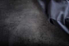 Schwarze Serviettentischdecke auf schwarzem konkretem Brett Lizenzfreie Stockfotografie