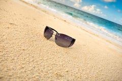 Schwarze Sonnegläser auf weißem Sand setzen nahe Meer auf den Strand Stockfotografie