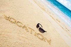 Schwarze Sonnegläser auf weißem Sandstrand Lizenzfreies Stockbild