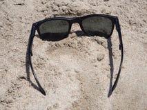 Schwarze Sonnenbrille auf dem Strand Stockfotos