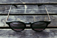 Schwarze Sonnenbrille auf Holztisch Stockfoto