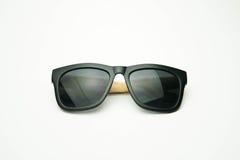 Schwarze Sonnenbrille mit den Holzbeinen auf weißem Hintergrund Stockbilder
