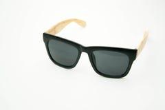 Schwarze Sonnenbrille mit den Holzbeinen auf weißem Hintergrund Lizenzfreies Stockfoto