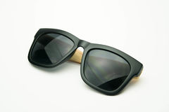 Schwarze Sonnenbrille mit den Holzbeinen auf weißem Hintergrund Stockfoto