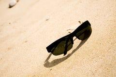 Schwarze Sonnenbrillen auf dem Sand stockfotos
