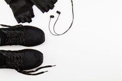Schwarze Sportschuhe, -handschuh und -kopfhörer auf weißem Hintergrund stockfotografie