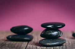 Schwarze Steinbehandlung auf einem Holztisch Badekurort und Wellneßkonzept Lizenzfreies Stockfoto