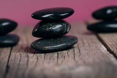 Schwarze Steinbehandlung auf einem Holztisch Badekurort und Wellneßkonzept Stockfotos