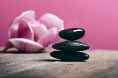 Schwarze Steinbehandlung auf einem Holztisch Badekurort und Wellneßkonzept Stockfoto