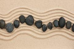 Schwarze Steine auf dem Sand Stockfoto